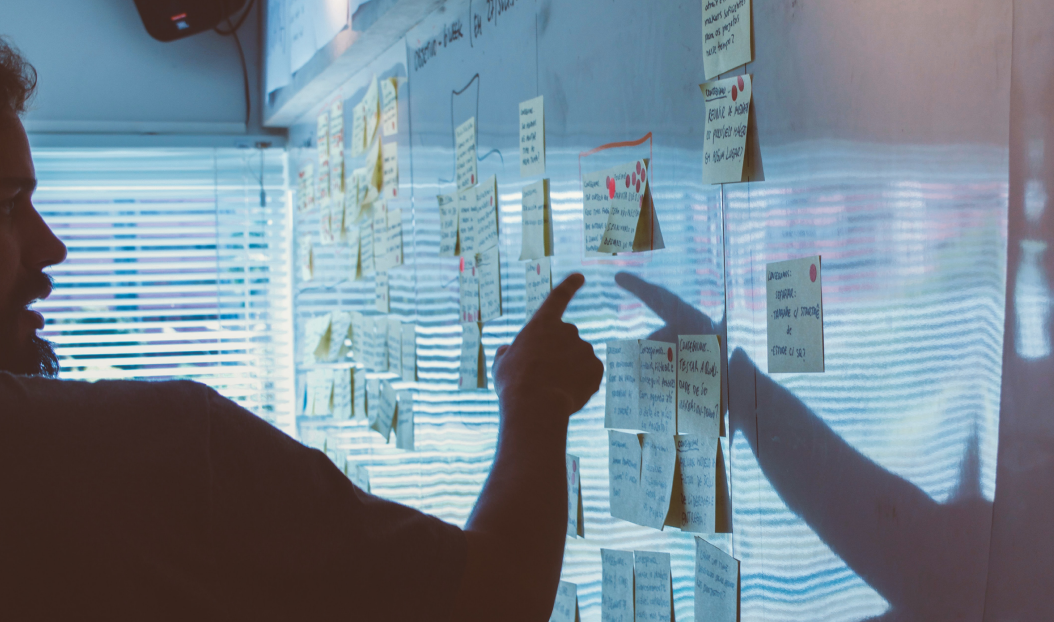 Man pointing at sticky notes on whiteboard